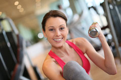 Happy young woman working out in a fitness center Royalty Free Stock Image