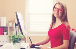 Young woman working with a pen tablet in her home office. Happy young woman working with a pen stylus tablet in her home office Royalty Free Stock Photo