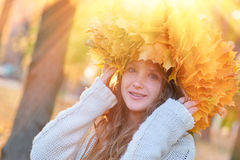 Happy young woman with a wreath of yellow leaves walking in the park.  royalty free stock image