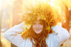Happy young woman with a wreath of yellow leaves walking in the park.  royalty free stock photo