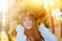 Happy young woman with a wreath of yellow leaves walking in the park.  stock photos