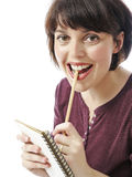 Happy young woman writes something to the workbook Royalty Free Stock Images