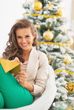 Happy young woman writing on envelope near christmas tree Royalty Free Stock Images