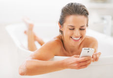 Happy young woman writing sms in bathtub Royalty Free Stock Photo