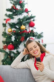 Happy young woman writing sms near Christmas tree Stock Photos