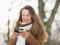 Happy young woman writing sms in winter outdoors Royalty Free Stock Images