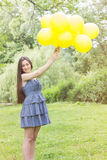Happy Young Woman With Yellow Balloons Stock Image