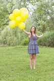 Happy Young Woman With Yellow Balloons Stock Photography