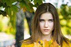 Happy young woman in yellow coat in autumn park Royalty Free Stock Images
