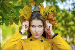Happy young woman in yellow coat in autumn park Royalty Free Stock Photo