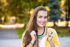 Happy young woman in yellow coat in autumn street Stock Images