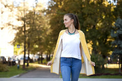 Happy young woman in yellow coat in autumn street Royalty Free Stock Photography