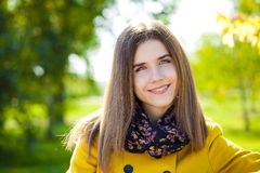 Happy young woman in yellow coat in autumn street Stock Photography