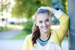 Happy young woman in yellow coat in autumn street Stock Image