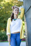 Happy young woman in yellow coat in autumn street Royalty Free Stock Photo