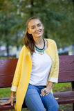 Happy young woman in yellow coat in autumn street Stock Photo