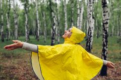 Happy young woman in yellow raincoat walking in spring forest under rain and having fun raising arms royalty free stock images