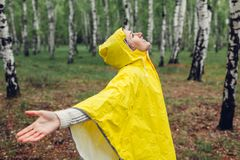 Happy young woman in yellow raincoat walking in spring forest under rain and having fun raising arms royalty free stock photo