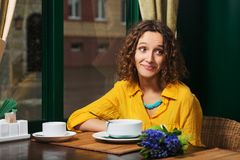 Happy young woman in yellow shirt eating a soup at restaurant royalty free stock photography