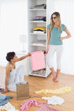 Happy young women arranging clothes in shelf Stock Image