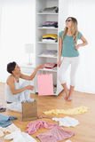 Happy young women arranging clothes in shelf Royalty Free Stock Photography