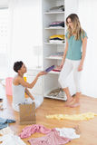Happy young women arranging clothes in shelf Royalty Free Stock Images