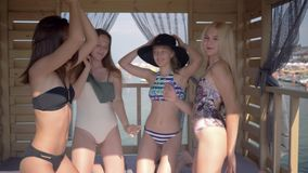 Happy young women with beautiful bodies have fun in a bungalow sing and dance on sea coast during the summer holidays