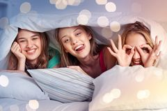 Happy young women in bed at home pajama party royalty free stock images