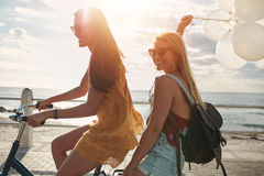 Happy young women on bike together with balloons. Happy young women riding a bicycle together with balloons. Best friends having fun on a cycle by the sea Stock Photo
