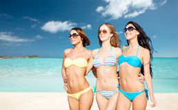 Happy young women in bikinis on summer beach Royalty Free Stock Photos