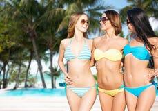 Happy young women in bikinis on summer beach Stock Image