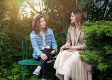 Happy young women chatting in park on greenery foliage background, lifestyle portrait.  stock image