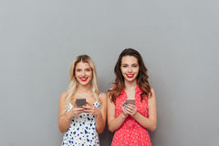 Happy young women chatting by phone. Royalty Free Stock Image