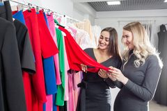 Happy young women choosing clothes in mall or clothing store. Sale, fashion, consumerism concept.  stock image
