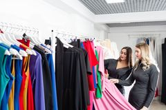 Happy young women choosing clothes in mall or clothing store. Sale, fashion, consumerism concept.  royalty free stock images