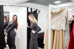 Happy young women choosing clothes in mall or clothing store. Sale, fashion, consumerism concept.  royalty free stock photos