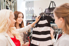 Happy young women choosing clothes in mall. Sale, consumerism and people concept - happy young women choosing clothes in mall Royalty Free Stock Photos