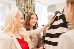 Happy young women choosing clothes in mall Royalty Free Stock Image