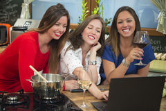 Happy young women cooking using laptop in the kitchen. Royalty Free Stock Photography