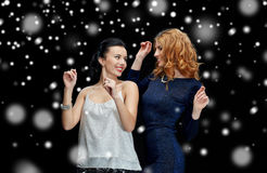 Happy young women dancing at night club disco. Party, holidays, nightlife and people concept - happy young women dancing at night club disco over black Stock Photography