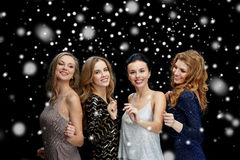Happy young women dancing at night club disco. Party, holidays, nightlife and people concept - happy young women dancing at night club disco over black Stock Images