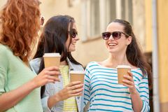Happy young women drinking coffee on city street Royalty Free Stock Image