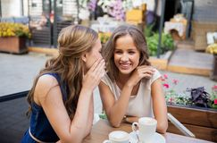 Happy young women drinking coffee at outdoor cafe Royalty Free Stock Photos