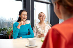 Happy young women drinking tea or coffee at cafe Royalty Free Stock Images
