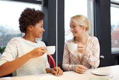 Happy young women drinking tea or coffee at cafe Stock Image