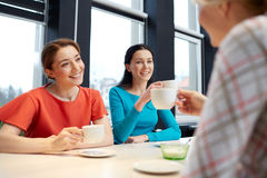 Happy young women drinking tea or coffee at cafe Stock Images