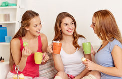 Happy young women drinking tea with sweets at home Stock Images