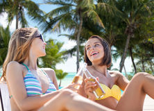 Happy young women with drinks sunbathing on beach Royalty Free Stock Image
