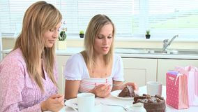 Happy young women eating chocolate cake. After shopping in the kitchen stock video footage