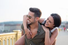 Happy young woman piggyback ride man outdoors in sunset royalty free stock image